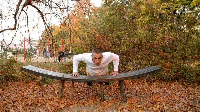 Boy exercise on a bench in a public park. video