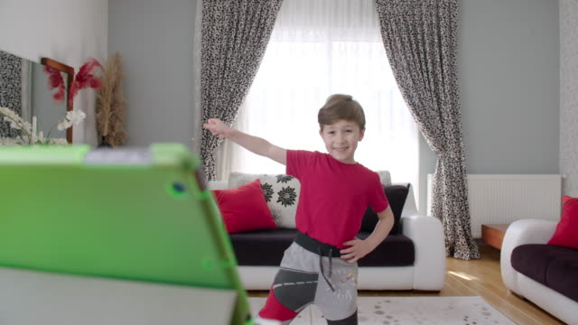 boy exercising in conjunction with a digital tablet - scolaro video stock e b–roll