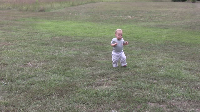 Boy falling and walking in grass video