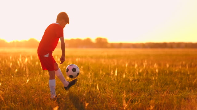 boy football player at sunset juggling the ball in the field - sci freestyle video stock e b–roll