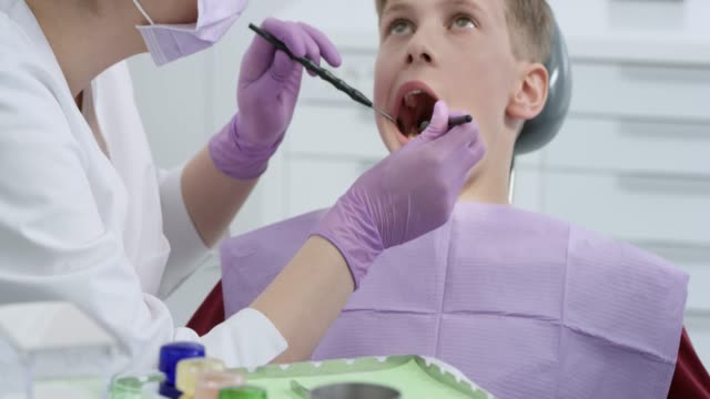 Boy getting his tooth repaired at the dentist's office video