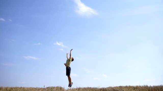 boy having fun against the sky, enjoying life, jumping for fun video