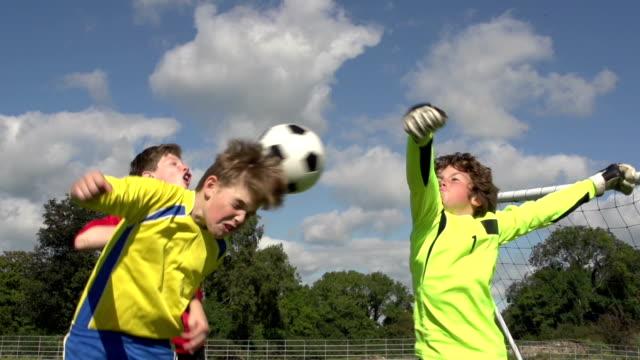 junge in richtung ziel im kid's soccer-super zeitlupe - geköpft stock-videos und b-roll-filmmaterial