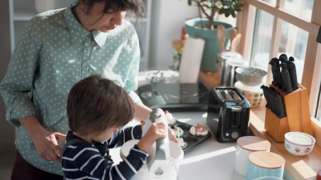 Boy Helping His Mother Mixing Whipped Cream Lovely Boy Using Electric Mixer With Help Of His Mom To Mix Whipped Cream appliance stock videos & royalty-free footage