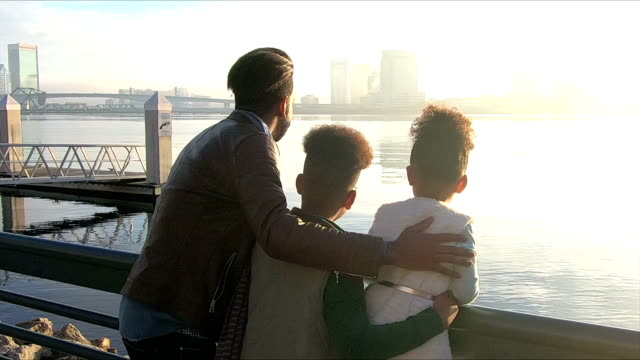 pojken att hjälpa syster, far anländer på city waterfront - strandnära bildbanksvideor och videomaterial från bakom kulisserna