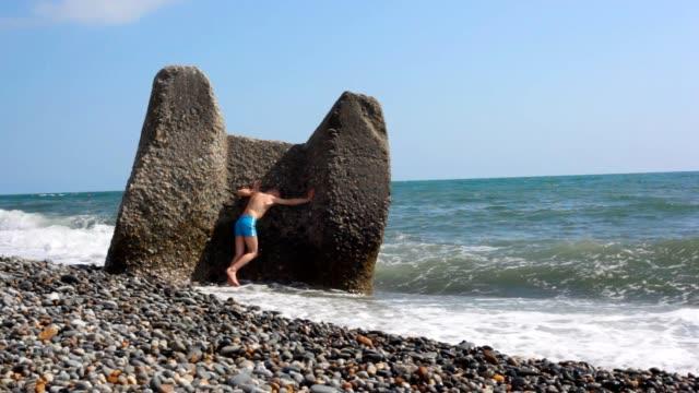 Boy hiding behind boulder in beach from sea surf video