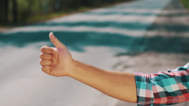 Boy hitchhiking at road in summer day. Tourist. Hold thumb up. Transportation video