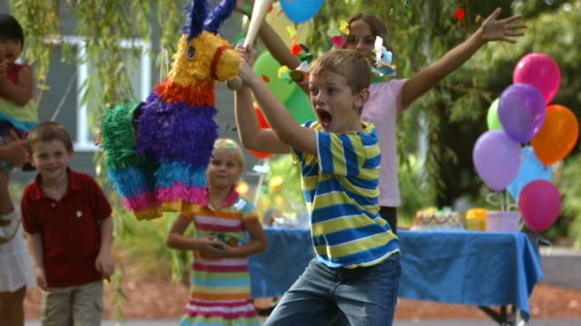Boy hitting a pinata at party, slow motion video