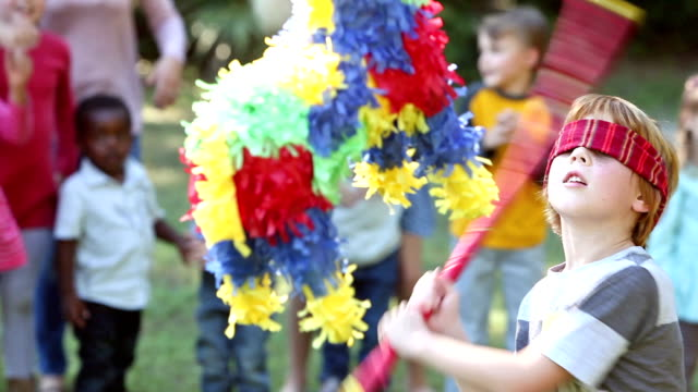Boy hitting pinata, children watching in background video
