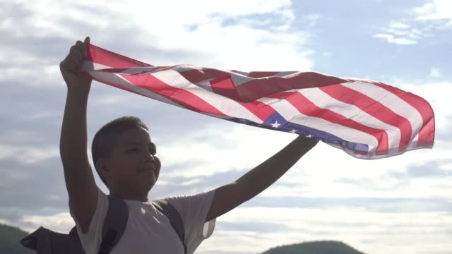 A boy holding American flag in the air blue sky