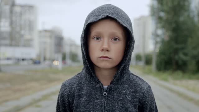 A boy in a black hood on the street