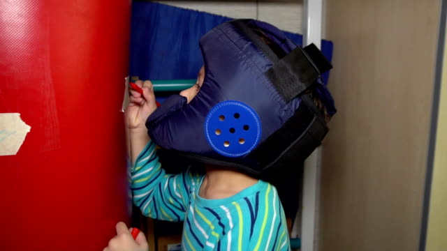 Boy in a boxing helmet paints a mark with a felt-tip pen for punches on punching bag video