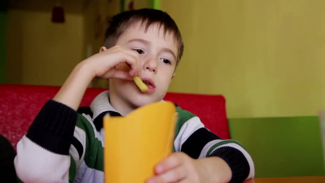 Boy in a cafe eating chips video