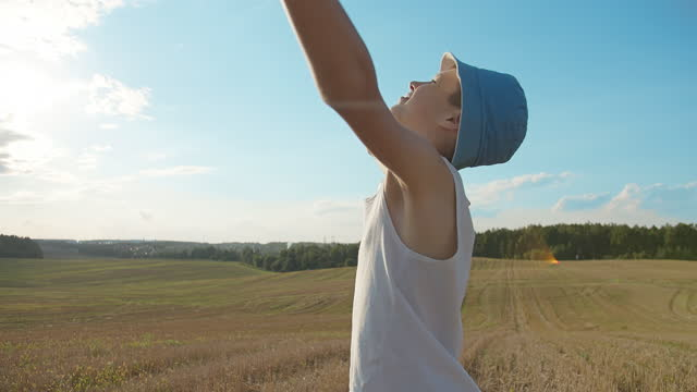 boy in a hat raises hands to the sky in the blue field video
