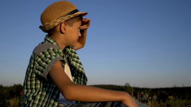 帽子の少年は丘の上に、慎重に距離、屋外に見える - 男の子点の映像素材/bロール