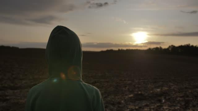 pojke i en huva ser in i fjärran på himlen vid solnedgången back view, närbild - på gränsen bildbanksvideor och videomaterial från bakom kulisserna