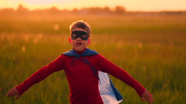 vídeos de stock e filmes b-roll de a boy in a suit and a superhero mask running across the field at sunset on the grass - baby super hero