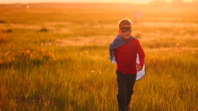 ein junge im anzug und eine superheldenmaske, die bei sonnenuntergang auf dem rasen über das feld läuft - held stock-videos und b-roll-filmmaterial