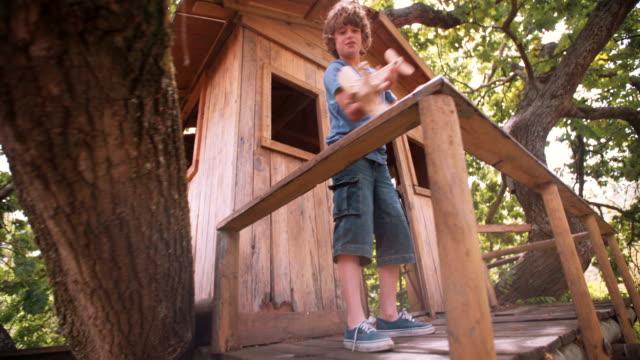 treehouse in un ragazzo giocando con un aereo giocattolo in legno - solo un bambino maschio video stock e b–roll