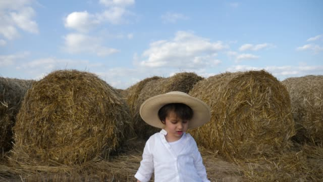 boy in a white shirt and a straw hat is barefoot on a sloping field - paglia video stock e b–roll