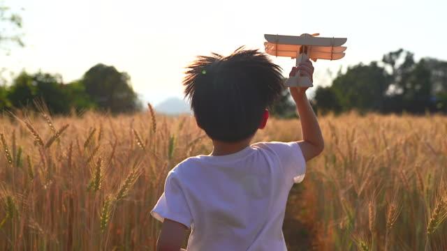 vídeos de stock, filmes e b-roll de um garoto de camisa branca segura um avião de brinquedo correndo no campo de trigo ele usou sua imaginação para pensar que era um piloto. corra livremente nos campos de trigo. - infância