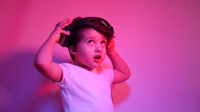 garçon dans un t-shirt blanc écoute la musique sur des écouteurs contre un mur - Vidéo