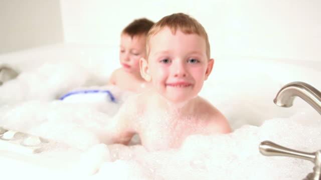 Junge in der Badewanne vergrößert Blasen in die Kamera. – Video