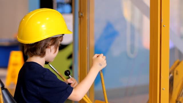 мальчик в шлем сидя в excavator builder - сельскохозяйственная машина стоковые видео и кадры b-roll