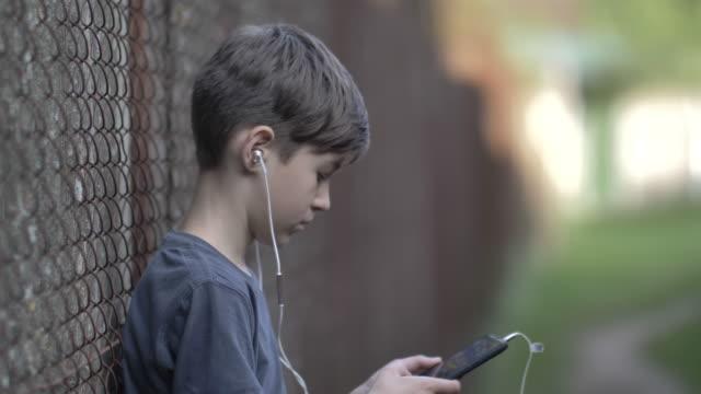 ヘッドフォンの少年は、携帯電話でフェンスの近くに立って、周りを見て、ゲームをプレイ - ゲーム ヘッドフォン点の映像素材/bロール