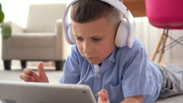 Boy in headphones using digital tablet on floor video