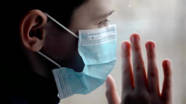 Pojke i medicinsk mask sätter sin hand på glas och ser tyvärr ut genom fönstret på gatan under korona pandemi video