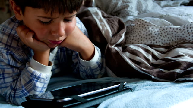 boy in pajamas in bed with tablet smiles video