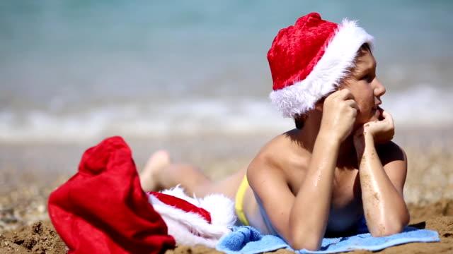 boy in Santa Claus hat on the beach
