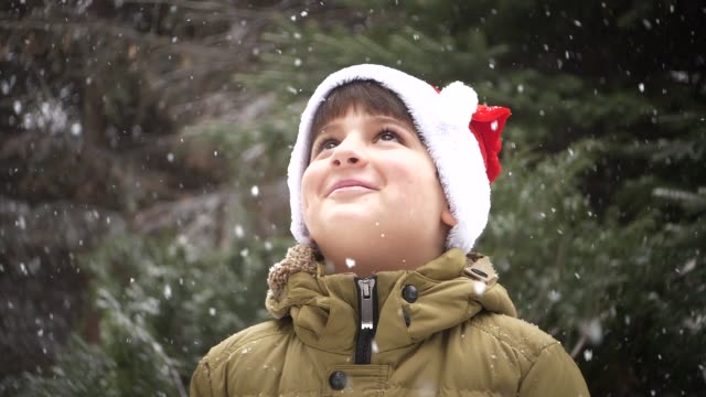 boy in santa claus hat smiles and looks at falling snow video