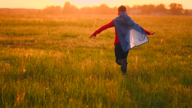 vídeos de stock e filmes b-roll de boy in superhero costume and mask running across the field at sunset dreaming and fantasizing - baby super hero