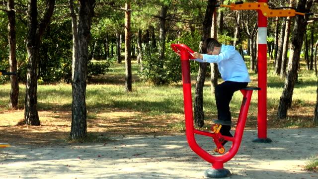Junge im Park auf einem stationären Fahrrad – Video