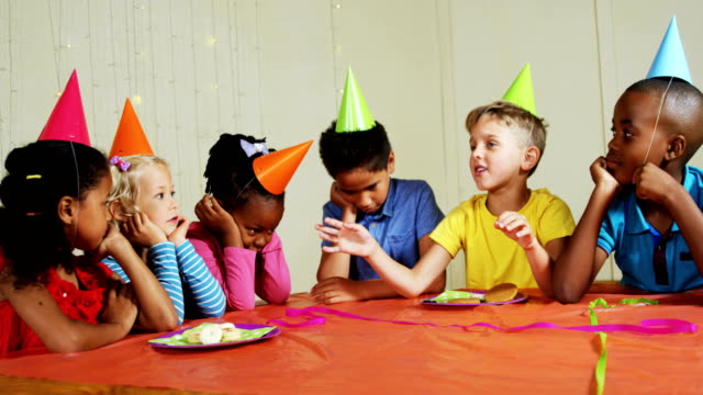Boy interacting with his friends during birthday party 4k video