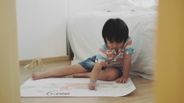 boy is drawing and crayon of dinosaur - matita colorata video stock e b–roll