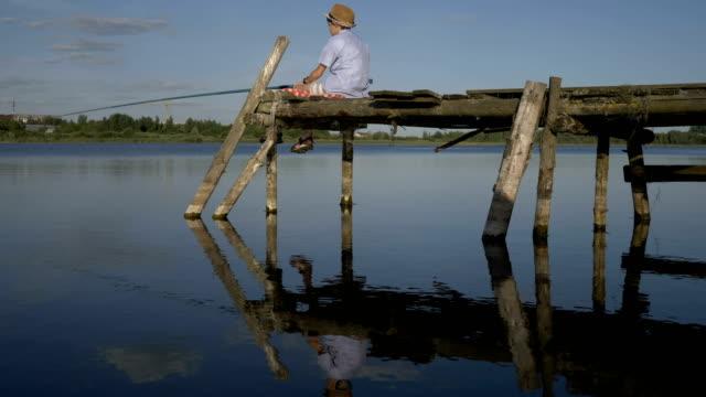 boy is fishing on the old pier in the river, outdoors - żabnicokształtne filmów i materiałów b-roll
