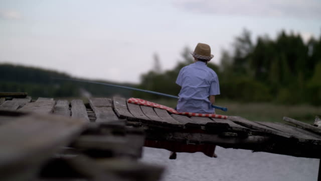 boy is fishing on the old pier in the river, outdoors - cappello video stock e b–roll