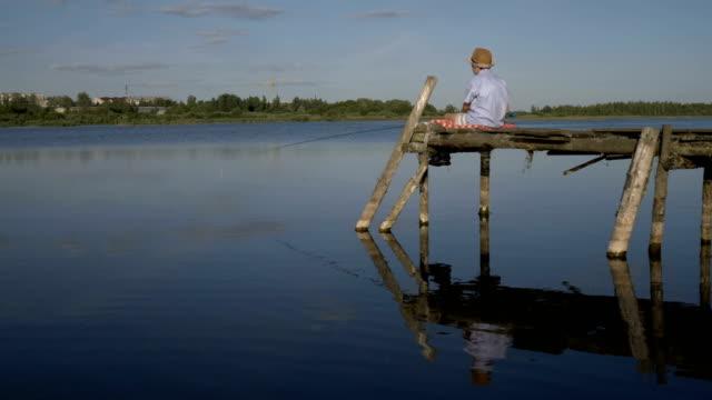 川で古い桟橋に少年は魚釣り - 漁師 外人点の映像素材/bロール