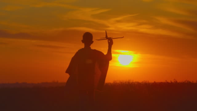 vídeos de stock e filmes b-roll de a boy is going across a field with a plane in his hand. sunset. 4k - baby super hero