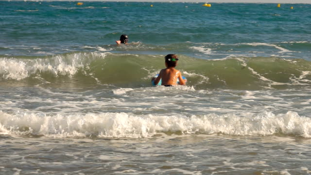 Boy is jumping on the sea waves with swimming board - video