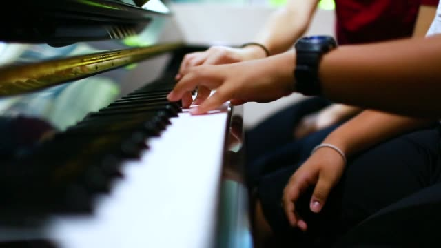 A boy is learning piano with woman teacher