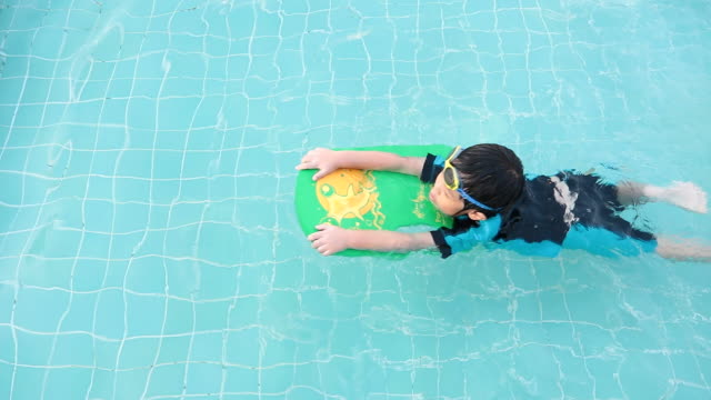 A boy is learning to swim to improve his swimming skills in the swimming pool with goggles and swimming foam for floating video