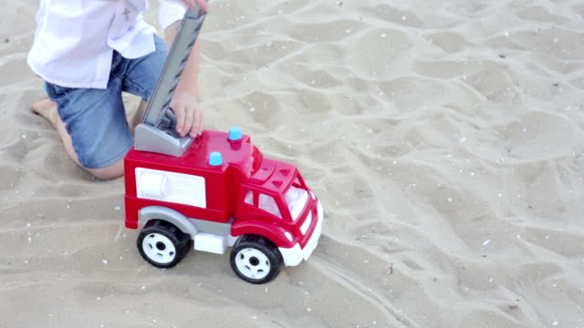 A boy is playing with a typewriter in the sand