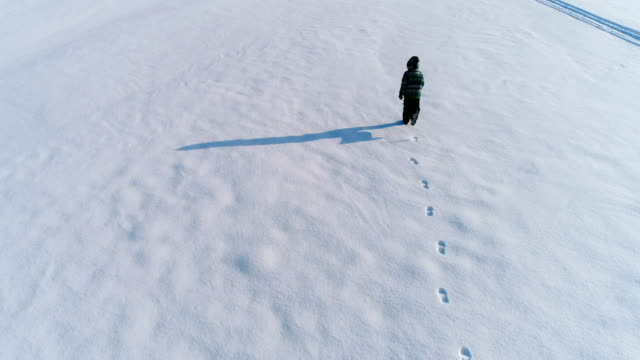 pojke som körs på ett snötäckt område, handpåläggning snön och gör snöängel, aerial film. - snow kids bildbanksvideor och videomaterial från bakom kulisserna