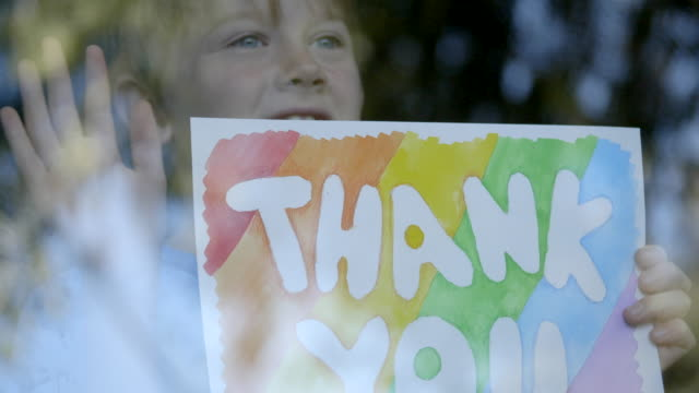 "Boy is showing ""THANK YOU"" drawing to doctors during quarantine for COVID-19 video"