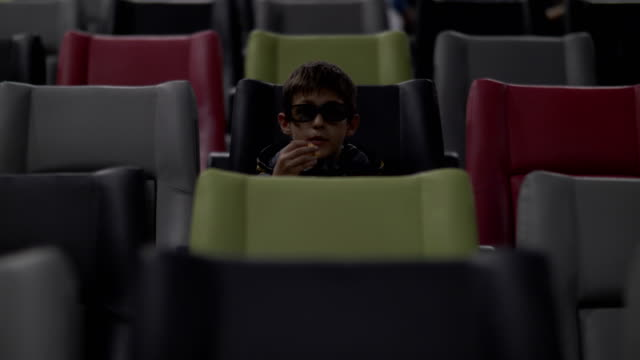 boy is sitting in the cinema watching film, eating popcorn video
