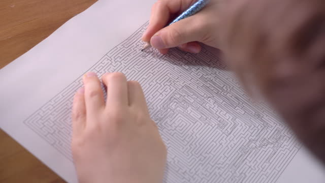 Boy is solving printed labyrinth on paper with pencil at home.